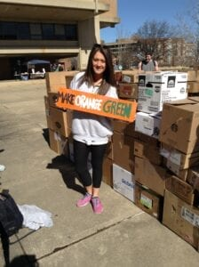 Creative director for the Up to Us campaign Carly Frensley holding up sign supporting its teammate club, UT Recycling.