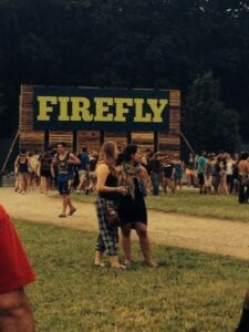 People gather at Firefly Music Festival in front of a Firefly sign.