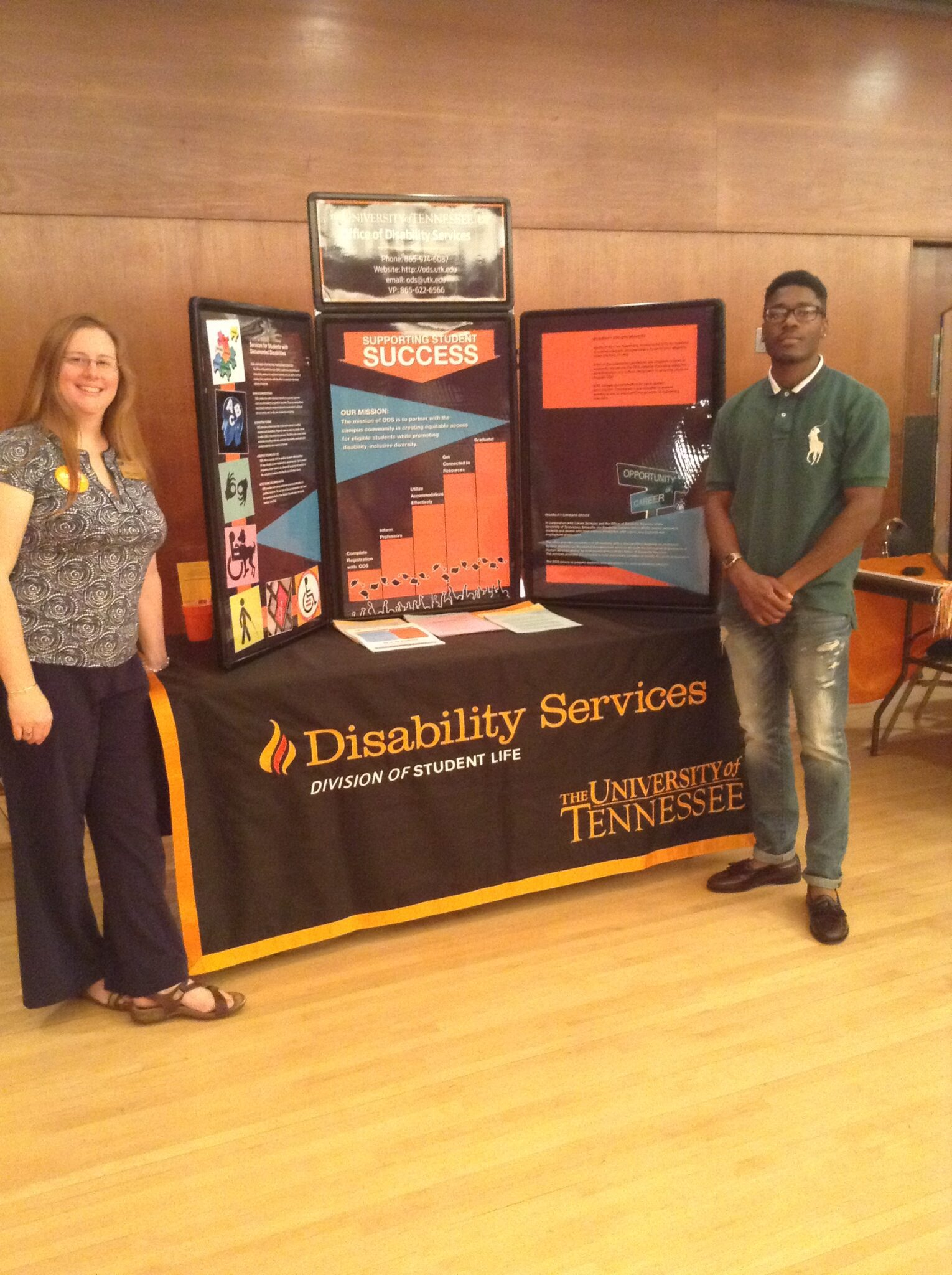 Sarah Bourque (left) and Emanuel Rollins, a verification specialist (right), standing beside the Office of Disability Services' booth