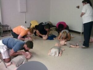 Students engaging in CPR training with the Clinic Vols