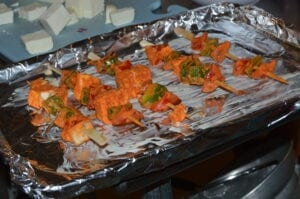 Paneer tikka, a traditional Indian appetizer, features marinated paneer cheese and vegetables.