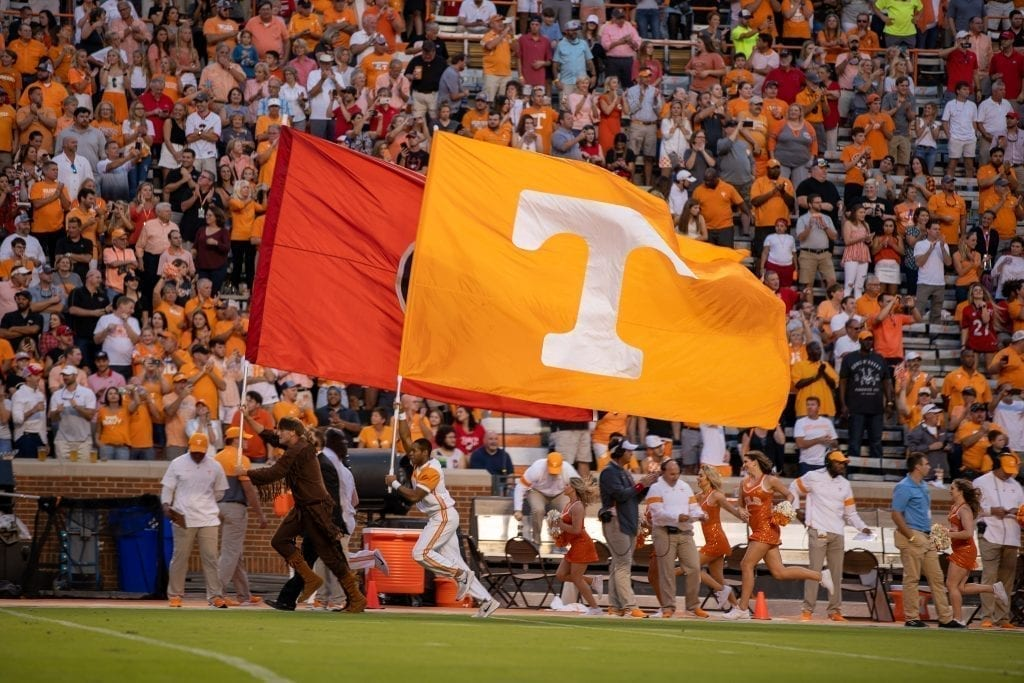 Tennessee cheerleaders run down the sideline holding Tennessee flags when Tennessee played Georgia in Neyland on Oct. 5. Photo/ Ben Gleason